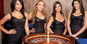 Live dealers behind a roulette wheel
